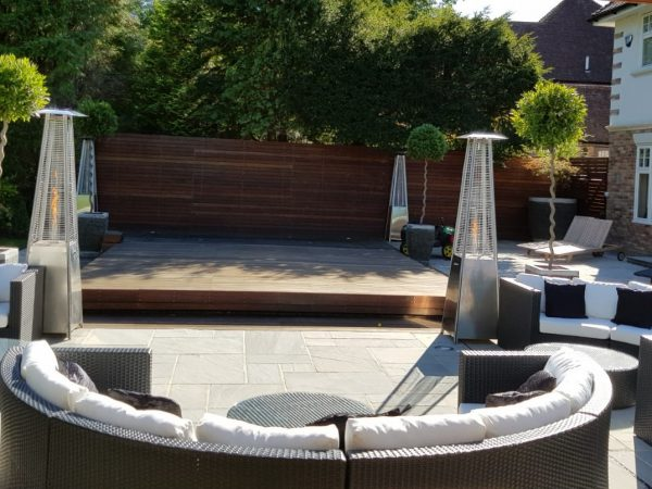 dark rattan curved sofa with silver patio heaters at garden party bbq