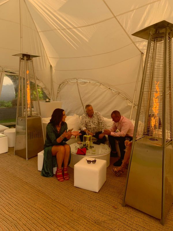 people sitting on white rattan curved sofa and white cubed seating with silver heaters at a garden party in a large tent