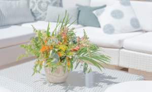 flower arrangement in foreground with white rattan outdoor sofa in background