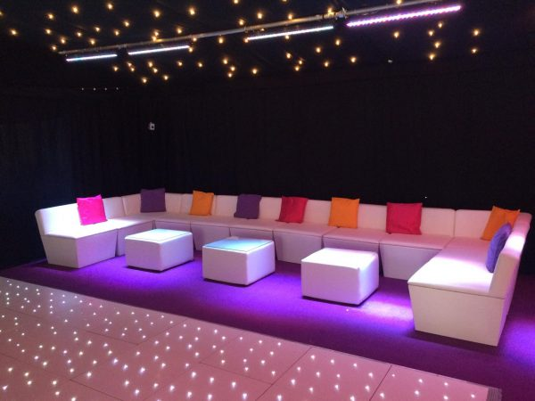 marquee furniture hire: white faux leather sofas and faux leather large cabo tables