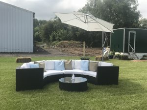 wedding sofa hire: curved rattan sofa outdoors